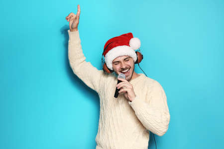 Young man in Santa hat singing into microphone on color background. Christmas music Stock Photo