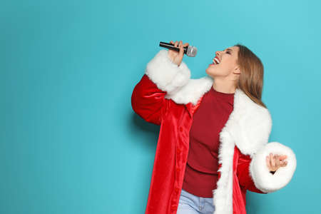 Young woman in Santa costume singing into microphone on color background. Christmas music