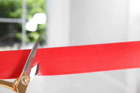 Ribbon and scissors on blurred background. Ceremonial red tape cutting