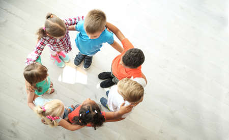 Little children making circle with hands around each other indoors, top view. Unity concept Imagens