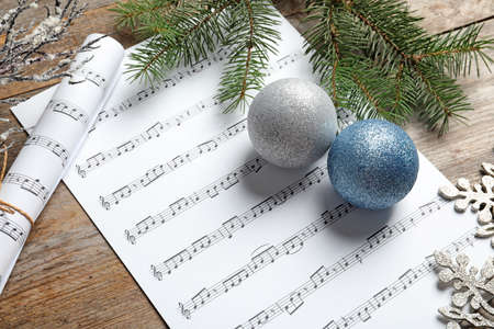 Composición con adornos navideños y partituras sobre fondo de madera Foto de archivo