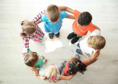 Małe dzieci, co koło z rękami wokół siebie w pomieszczeniu, widok z góry. Koncepcja jedności