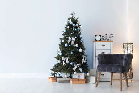 Stylish living room interior with decorated Christmas tree and comfortable armchair 스톡 콘텐츠