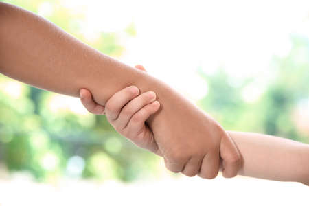 Children holding hands on blurred background, closeup. Unity concept