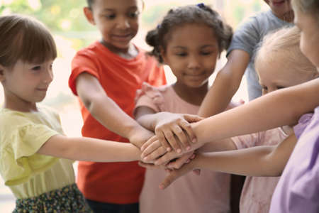 Los niños pequeños juntan las manos, en el interior. Concepto de unidad Foto de archivo