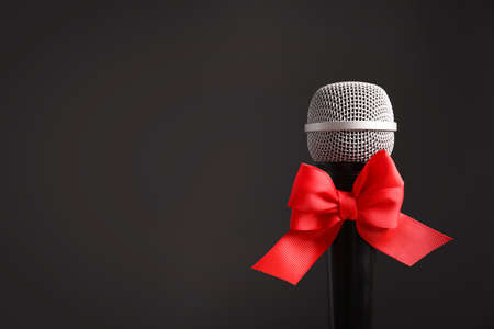 Microphone with bow on black background. Christmas music concept