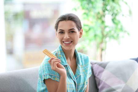 Mujer joven con pastillas anticonceptivas en casa. Ginecología