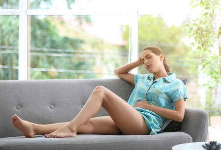 Young woman suffering from menstrual cramps at home. Gynecology Stock Photo