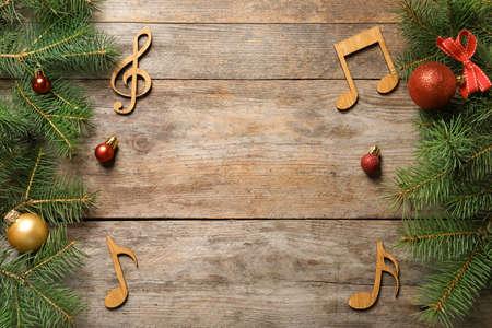 Composición laicos plana con decoraciones y notas sobre fondo de madera. Concepto de música navideña Foto de archivo
