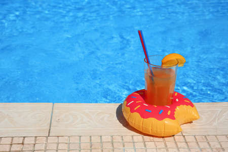 Tasty refreshing cocktail on edge of swimming pool