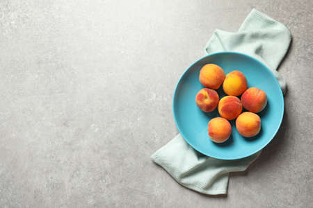 Plate with fresh sweet peaches on table, top view