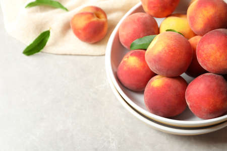 Plates with fresh sweet peaches on table Фото со стока