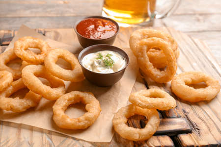 Fried onion rings served with sauces on wooden board, closeup Stock Photo