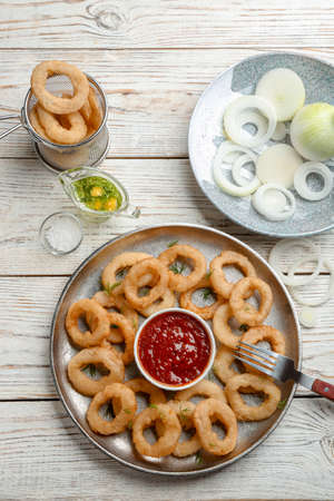 Flat lay composition with onion rings on wooden background