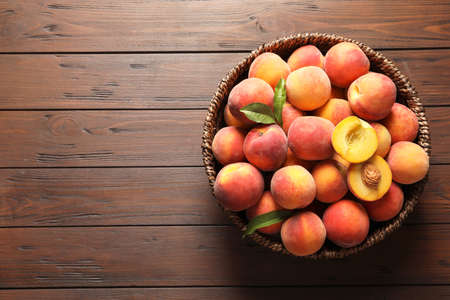 Wicker basket with fresh sweet peaches on wooden table, top view 写真素材