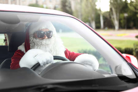 Authentic Santa Claus in sunglasses driving car, view from outside