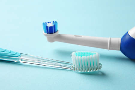Manual and electric toothbrushes on color background. Dental care