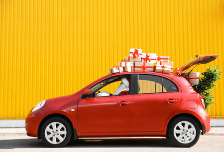 Authentic Santa Claus driving red car with gift boxes and Christmas tree, view from outside Stock Photo
