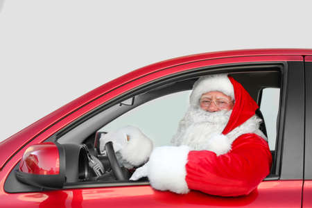 Authentic Santa Claus driving red car, view from outside Banco de Imagens