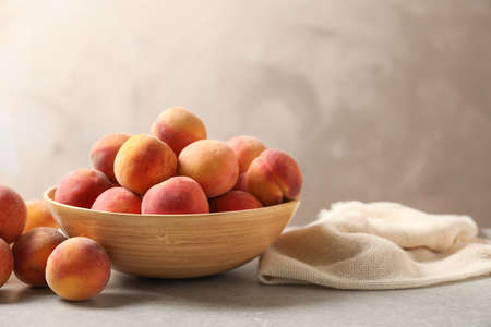 Delicious ripe peaches on table against grey background Stockfoto