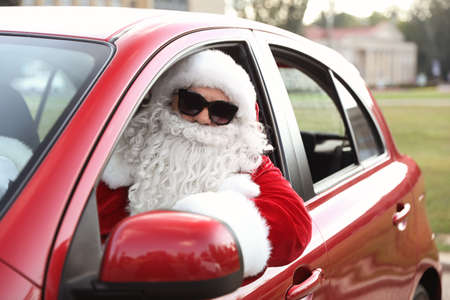 Authentic Santa Claus with sunglasses driving car, view from outside