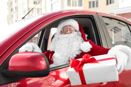 Authentic Santa Claus with gift box driving car, view from outside Stock Photo