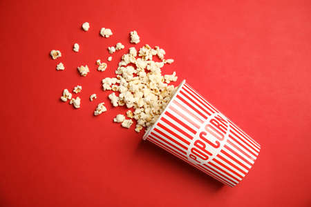 Paper cup with tasty fresh popcorn on color background, top view
