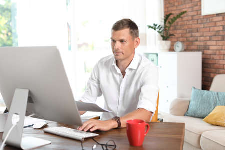 Young man working with computer in home office