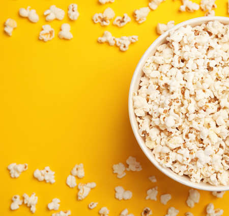 Paper bucket with tasty fresh popcorn on color background, top view Foto de archivo
