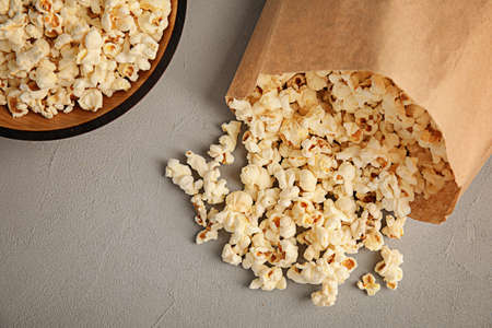 Paper bag and bowl with tasty popcorn on grey background, top view