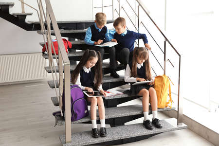 Little children in stylish school uniform on stairs indoors Фото со стока