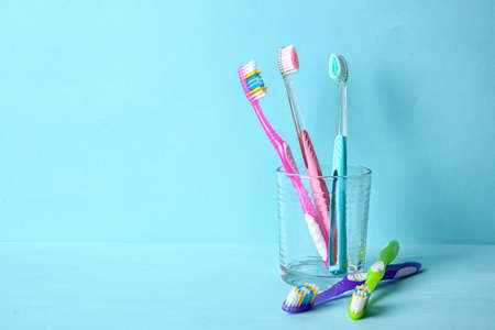 Cup with toothbrushes on color background. Dental care Stock Photo