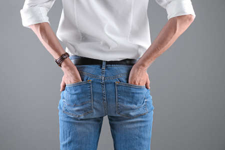 Man in stylish blue jeans on grey background Stock Photo