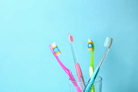 Cup with toothbrushes against color background. Dental care Stock Photo