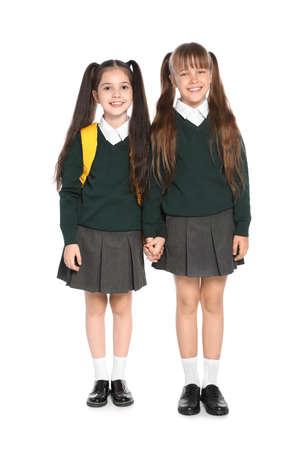 Little girls in stylish school uniform on white background