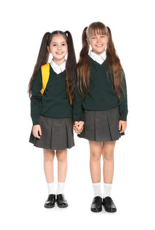Little girls in stylish school uniform on white background