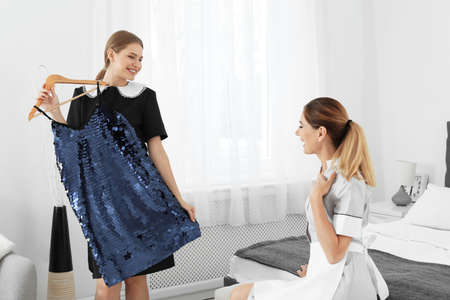 Young chambermaids trying on clothes in a room
