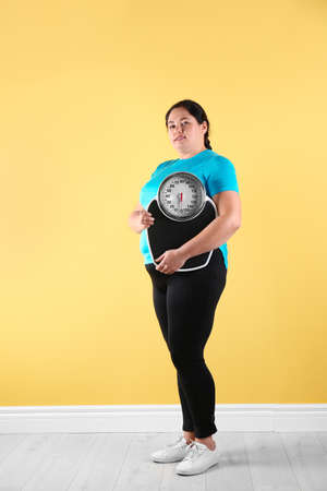 Overweight woman in sportswear with scales near color wall