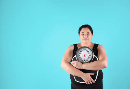 Overweight woman in sportswear with scales on color background Stock Photo