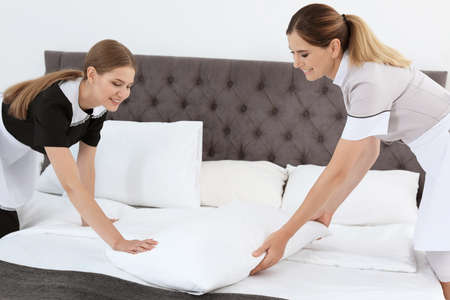 Professional chambermaids making bed in a room
