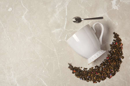 Flat lay composition with dry tea and cup on grey background