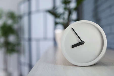 Analog alarm clock on table at home. Time of day Archivio Fotografico