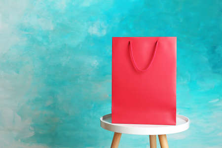 Mockup of paper shopping bag on table against color background