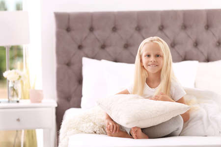 Cute little girl with pillow sitting on bed at home Stockfoto
