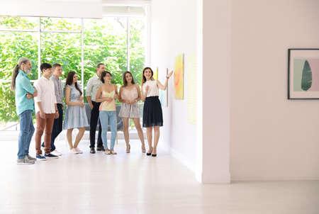 Grupa osób z przewodnikiem na wystawie w galerii sztuki