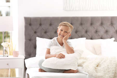 Cute little boy with pillow sitting on bed at home