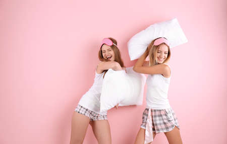 Two young women having pillow fight against color background Фото со стока