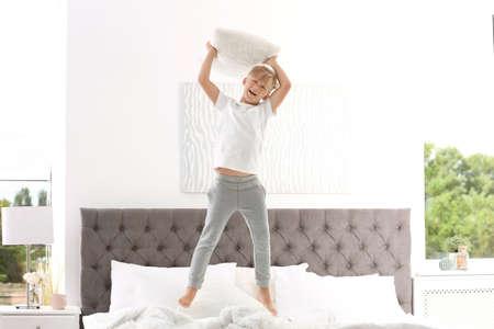 Cute little boy with pillow jumping on bed at home Stok Fotoğraf