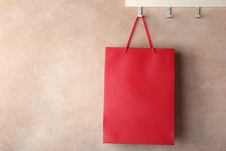 Rack with paper shopping bag on color wall. Mockup for design
