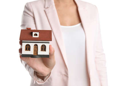 Real estate agent holding house model on white background Stock Photo